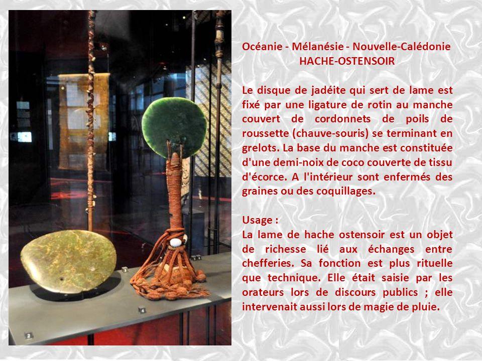 Océanie - Mélanésie - Nouvelle-Calédonie HACHE-OSTENSOIR Le disque de jadéite qui sert de lame est fixé par une ligature de rotin au manche couvert de cordonnets de poils de roussette (chauve-souris) se terminant en grelots.