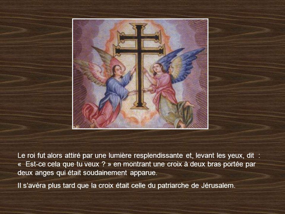 Le roi fut alors attiré par une lumière resplendissante et, levant les yeux, dit : « Est-ce cela que tu veux » en montrant une croix à deux bras portée par deux anges qui était soudainement apparue.