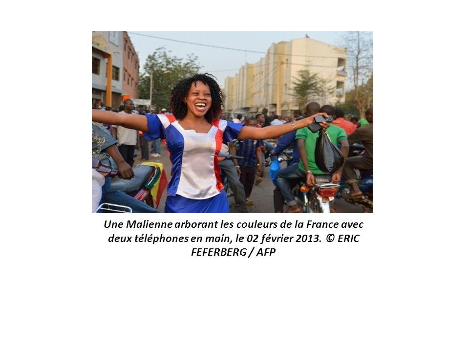 Une Malienne arborant les couleurs de la France avec deux téléphones en main, le 02 février 2013.