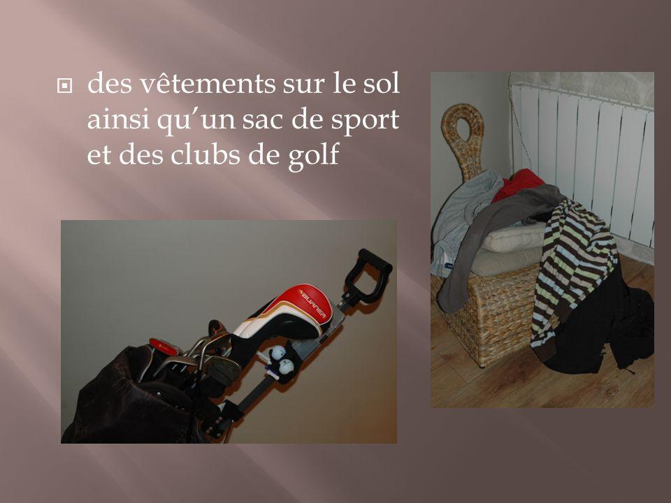 des vêtements sur le sol ainsi qu'un sac de sport et des clubs de golf
