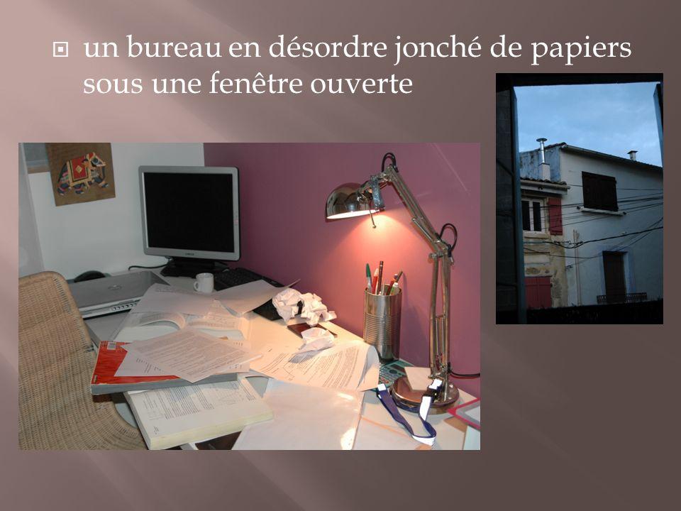un bureau en désordre jonché de papiers sous une fenêtre ouverte