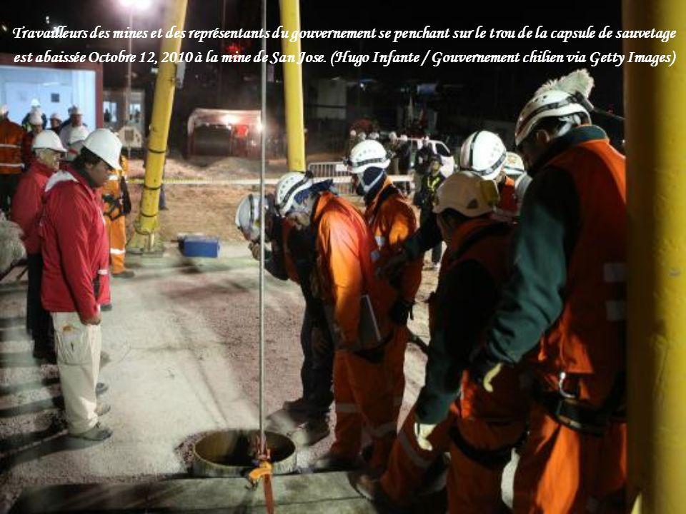 Travailleurs des mines et des représentants du gouvernement se penchant sur le trou de la capsule de sauvetage
