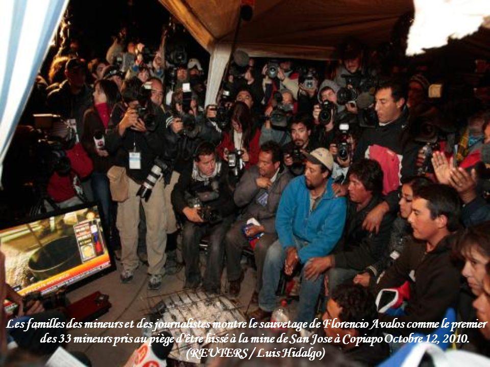 Les familles des mineurs et des journalistes montre le sauvetage de Florencio Avalos comme le premier des 33 mineurs pris au piège d être hissé à la mine de San Jose à Copiapo Octobre 12, 2010.