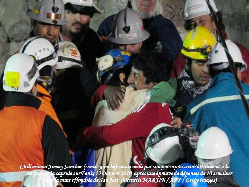 Chili mineur Jimmy Sanchez (centre gauche) est accueilli par son père après avoir été ramené à la surface de la capsule sur Fenix 13 Octobre 2010, après une épreuve de dépenses de 10 semaines dans la mine effondrée de San Jose.