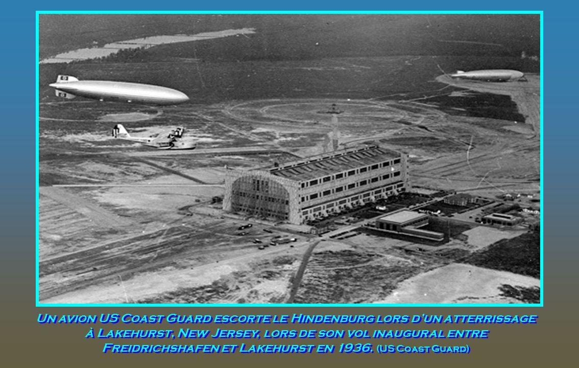 Un avion US Coast Guard escorte le Hindenburg lors d'un atterrissage à Lakehurst, New Jersey, lors de son vol inaugural entre Freidrichshafen et Lakehurst en 1936.