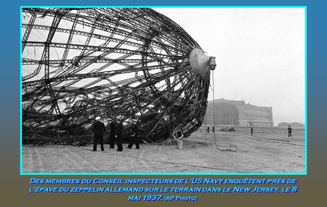 Des membres du Conseil inspecteurs de l US Navy enquêtent près de l épave du zeppelin allemand sur le terrain dans le New Jersey, le 8 mai 1937.