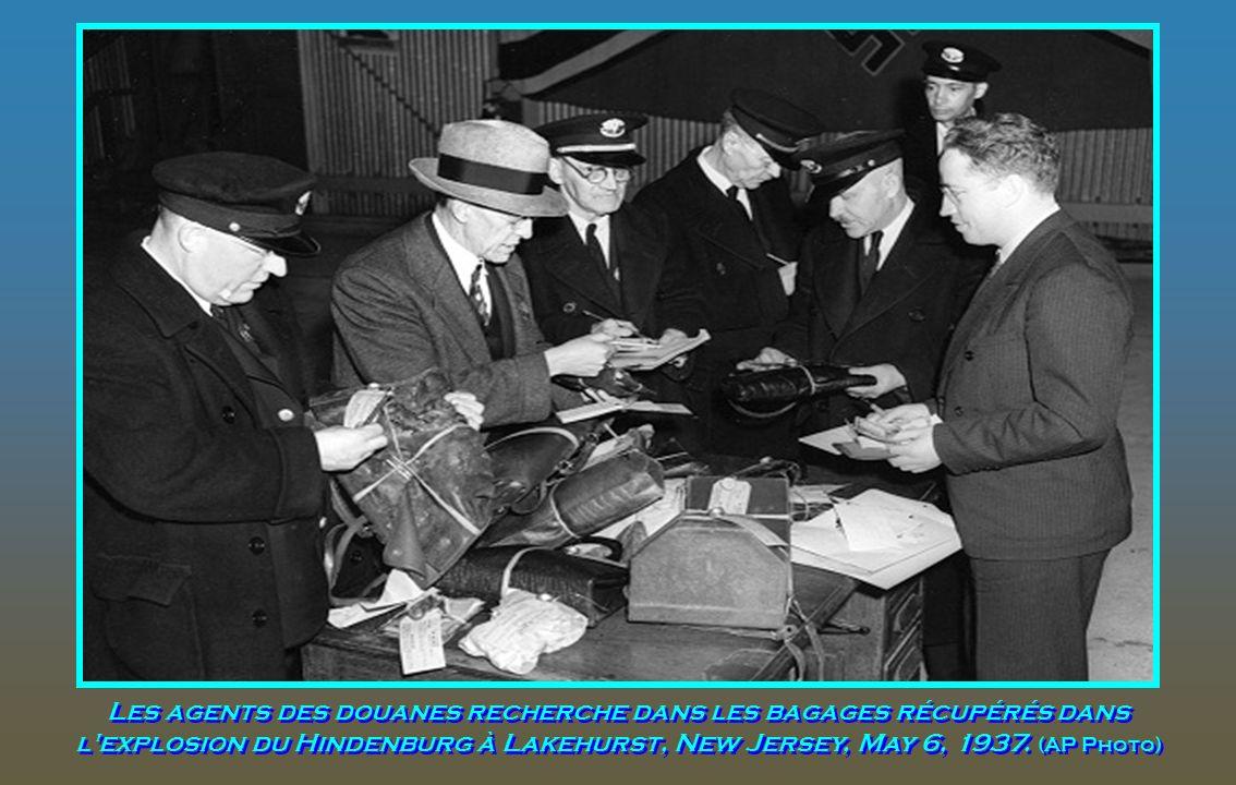 Les agents des douanes recherche dans les bagages récupérés dans l explosion du Hindenburg à Lakehurst, New Jersey, May 6, 1937.