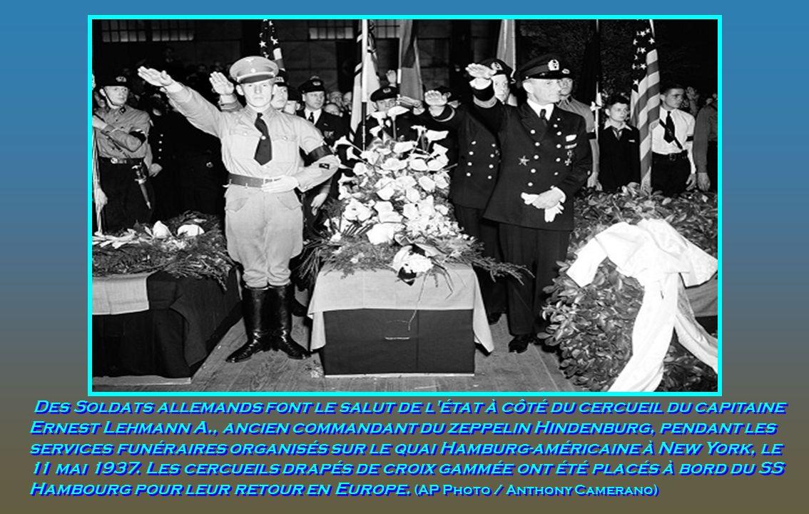 Des Soldats allemands font le salut de l état à côté du cercueil du capitaine Ernest Lehmann A., ancien commandant du zeppelin Hindenburg, pendant les services funéraires organisés sur le quai Hamburg-américaine à New York, le 11 mai 1937.