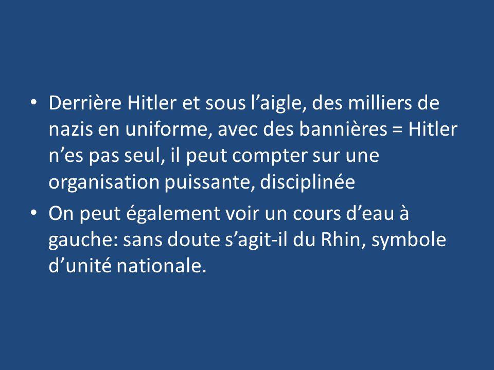 Derrière Hitler et sous l'aigle, des milliers de nazis en uniforme, avec des bannières = Hitler n'es pas seul, il peut compter sur une organisation puissante, disciplinée