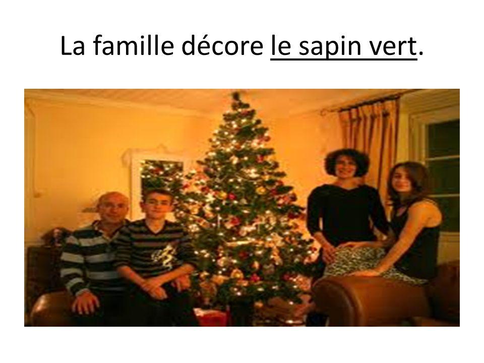 La famille décore le sapin vert.