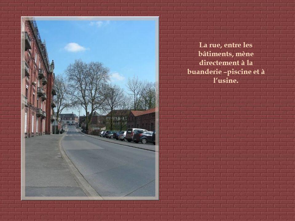 La rue, entre les bâtiments, mène directement à la buanderie –piscine et à l'usine.