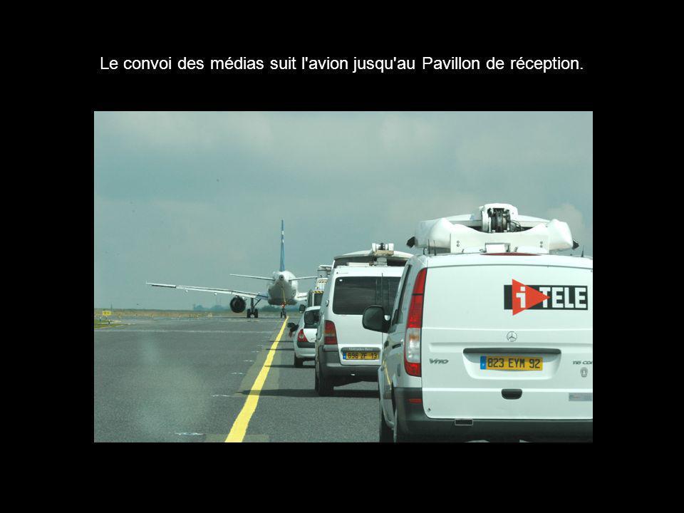 Le convoi des médias suit l avion jusqu au Pavillon de réception.