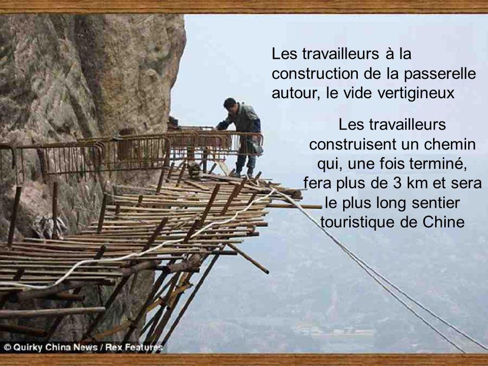 Les travailleurs à la construction de la passerelle autour, le vide vertigineux