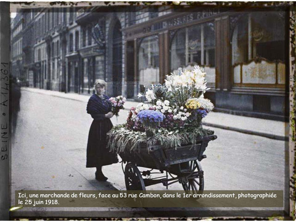 Ici, une marchande de fleurs, face au 53 rue Cambon, dans le 1er arrondissement, photographiée le 25 juin 1918.