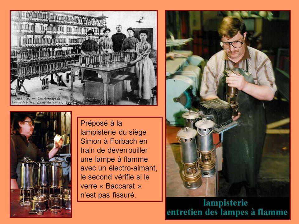 Préposé à la lampisterie du siège Simon à Forbach en train de déverrouiller une lampe à flamme avec un électro-aimant, le second vérifie si le verre « Baccarat » n'est pas fissuré.