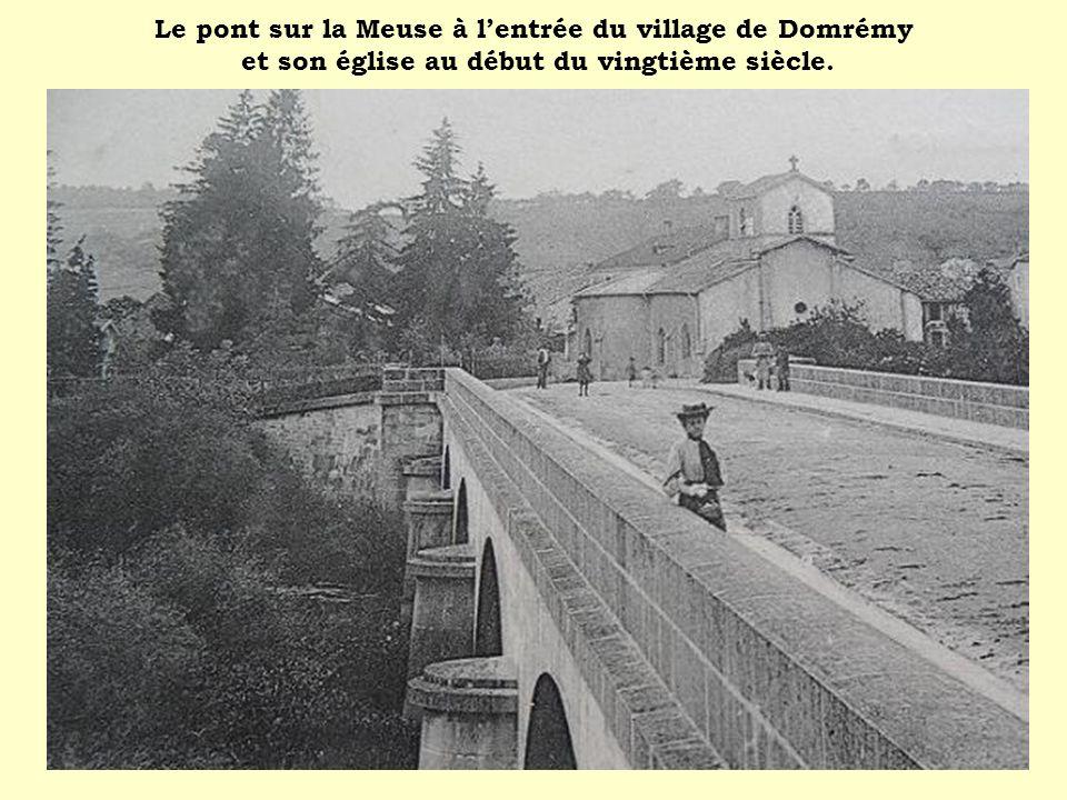 Le pont sur la Meuse à l'entrée du village de Domrémy et son église au début du vingtième siècle.