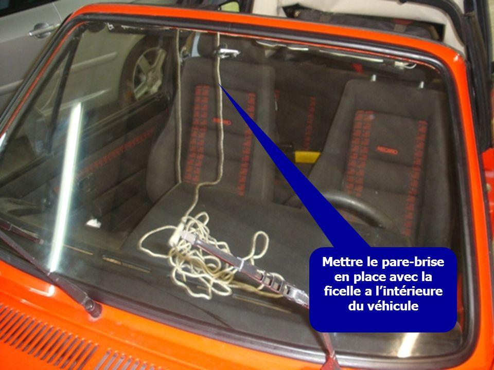 Mettre le pare-brise en place avec la ficelle a l'intérieure du véhicule