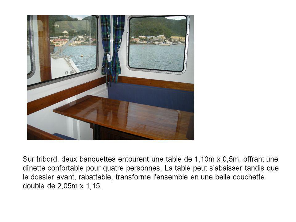 Sur tribord, deux banquettes entourent une table de 1,10m x 0,5m, offrant une dînette confortable pour quatre personnes.