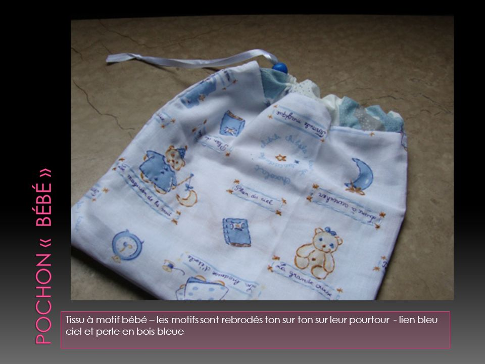 Pochon « bébé » Tissu à motif bébé – les motifs sont rebrodés ton sur ton sur leur pourtour - lien bleu ciel et perle en bois bleue.