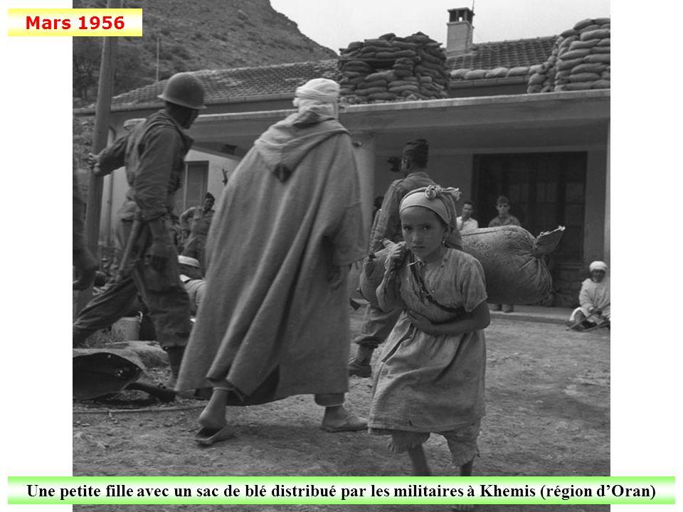 Mars 1956 Une petite fille avec un sac de blé distribué par les militaires à Khemis (région d'Oran)