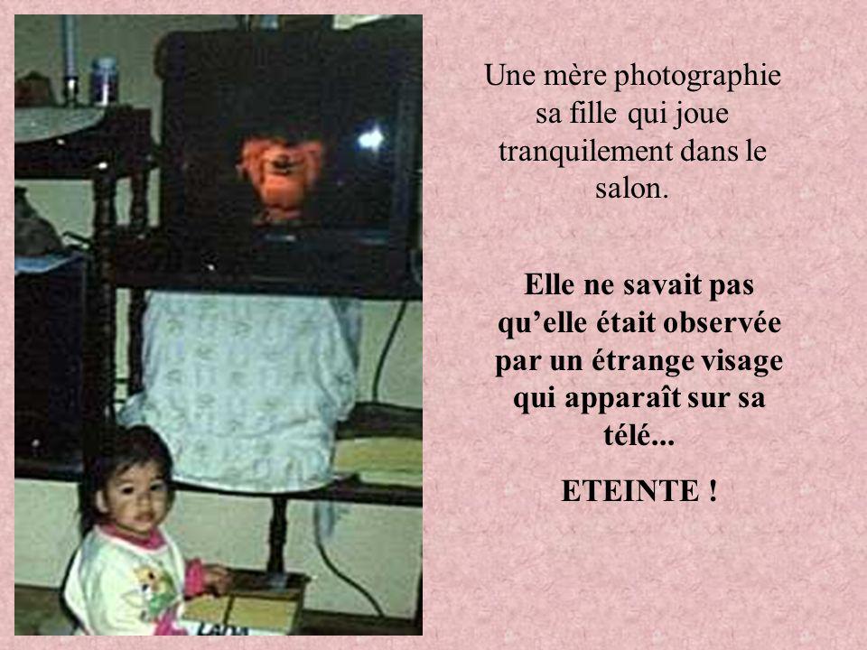 Une mère photographie sa fille qui joue tranquilement dans le salon.