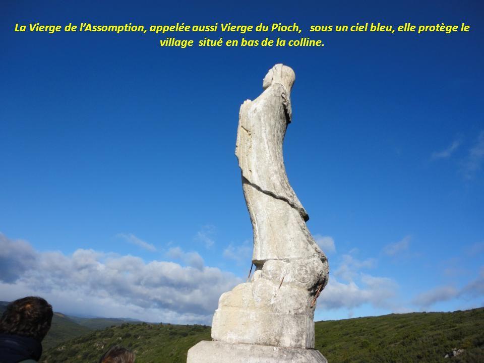 La Vierge de l'Assomption, appelée aussi Vierge du Pioch, sous un ciel bleu, elle protège le village situé en bas de la colline.