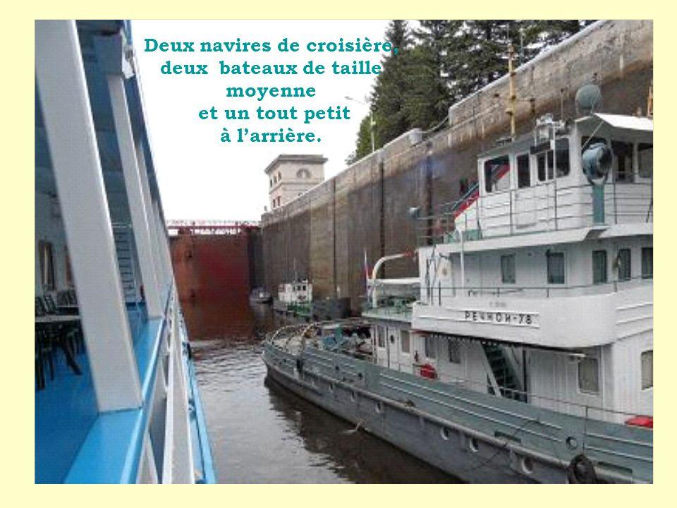 Deux navires de croisière, deux bateaux de taille moyenne et un tout petit à l'arrière.