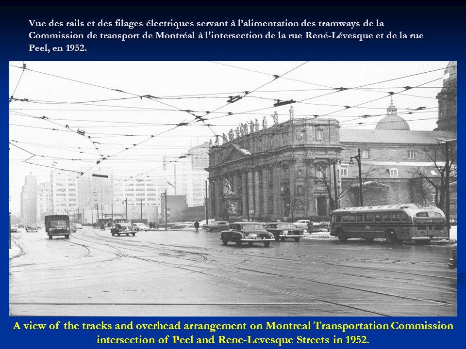 Vue des rails et des filages électriques servant à l'alimentation des tramways de la Commission de transport de Montréal à l intersection de la rue René-Lévesque et de la rue Peel, en 1952.