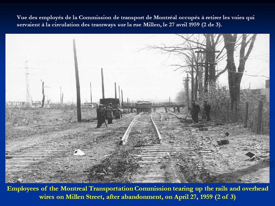 Vue des employés de la Commission de transport de Montréal occupés à retirer les voies qui servaient à la circulation des tramways sur la rue Millen, le 27 avril 1959 (2 de 3).