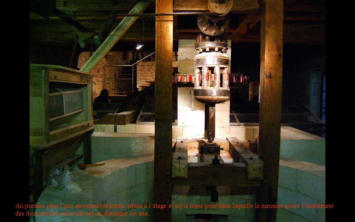 Au premier plan l'axe entraînant la meule située à l'étage et ici la fosse pour dans laquelle le meunier ajuste l'écartement des deux meules en soulevant ou abaissant cet axe.