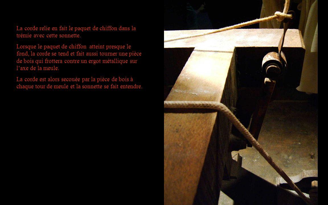 La corde relie en fait le paquet de chiffon dans la trémie avec cette sonnette.