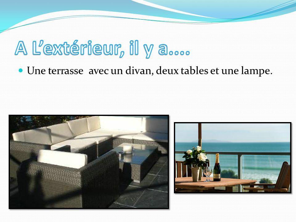 A L'extérieur, il y a.... Une terrasse avec un divan, deux tables et une lampe.