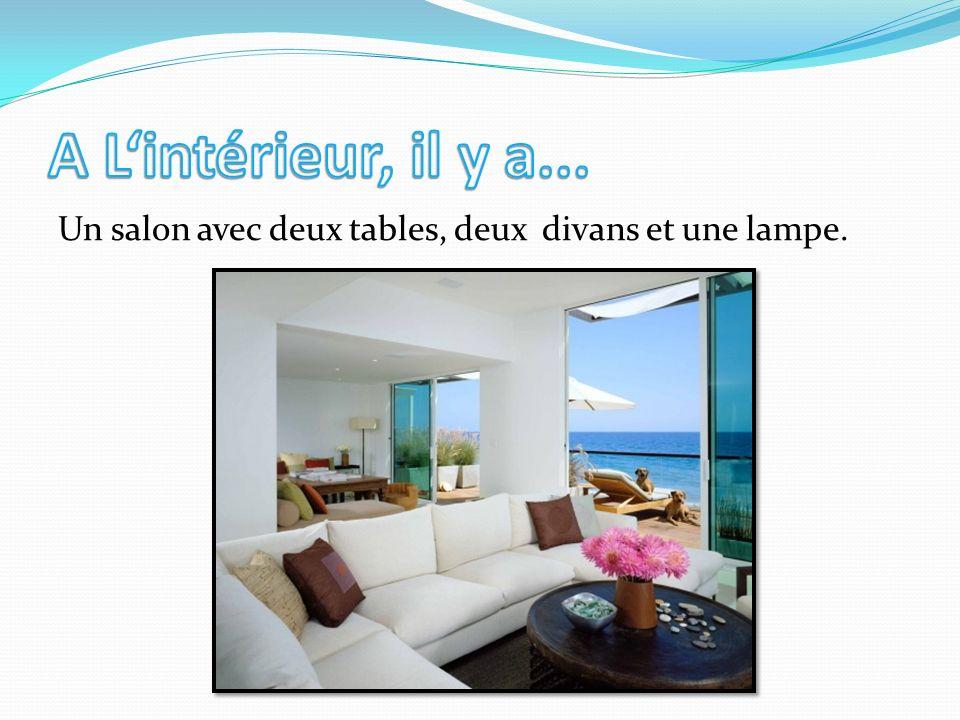 A L'intérieur, il y a... Un salon avec deux tables, deux divans et une lampe.