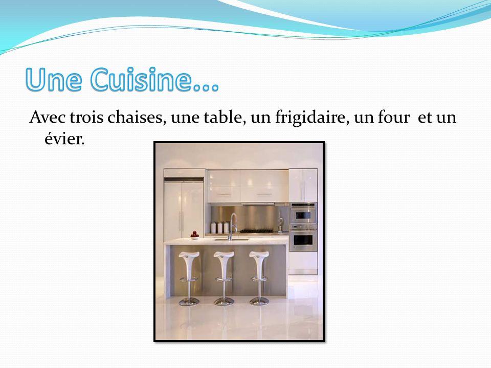 Une Cuisine... Avec trois chaises, une table, un frigidaire, un four et un évier.