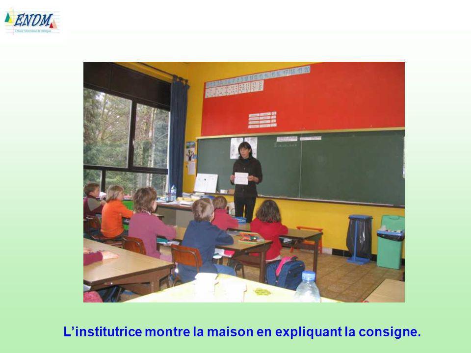 L'institutrice montre la maison en expliquant la consigne.