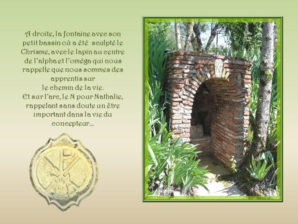 A droite, la fontaine avec son petit bassin où a été sculpté le Chrisme, avec le lapin au centre de l'alpha et l'oméga qui nous rappelle que nous sommes des apprentis sur