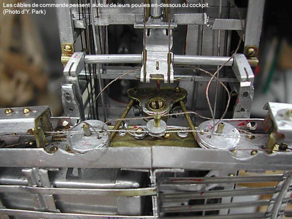 Les câbles de commande passent autour de leurs poulies en-dessous du cockpit.