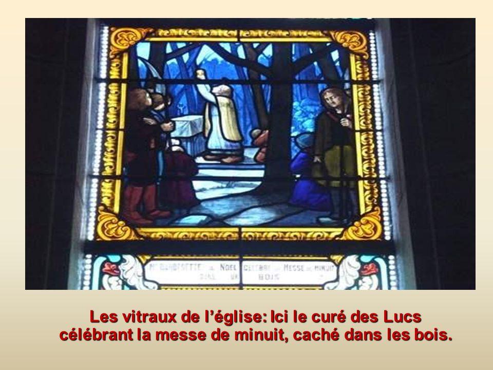 Les vitraux de l'église: Ici le curé des Lucs célébrant la messe de minuit, caché dans les bois.