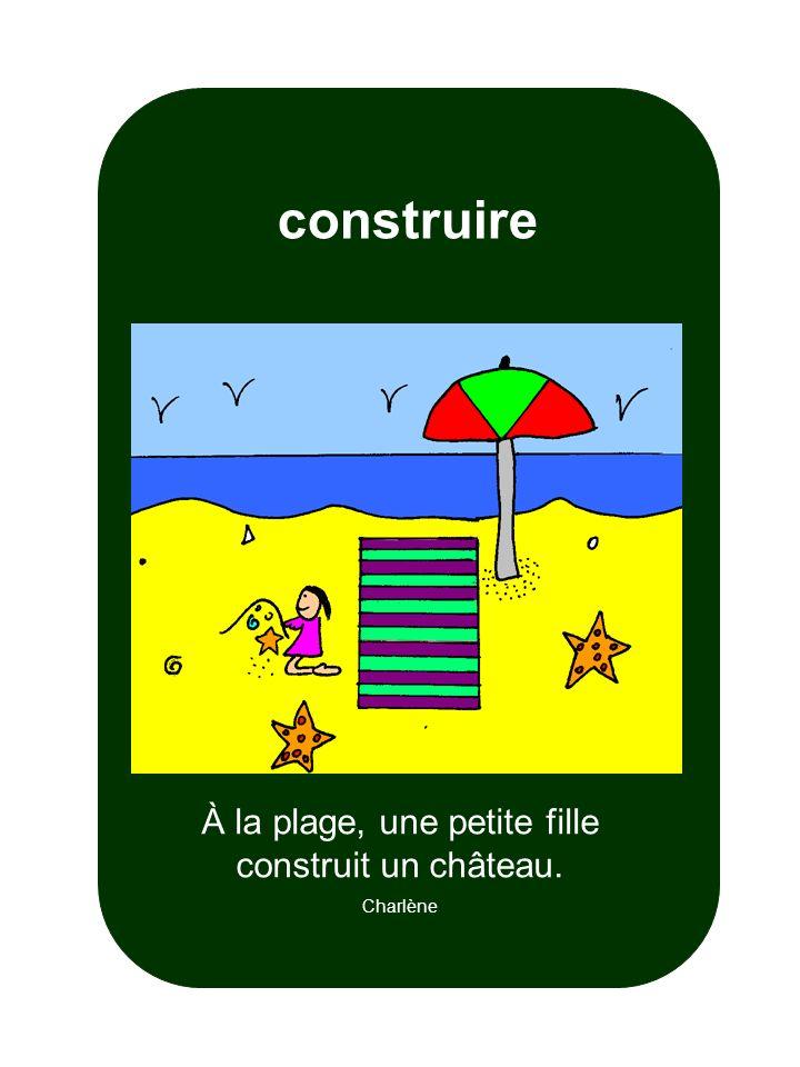 À la plage, une petite fille construit un château.