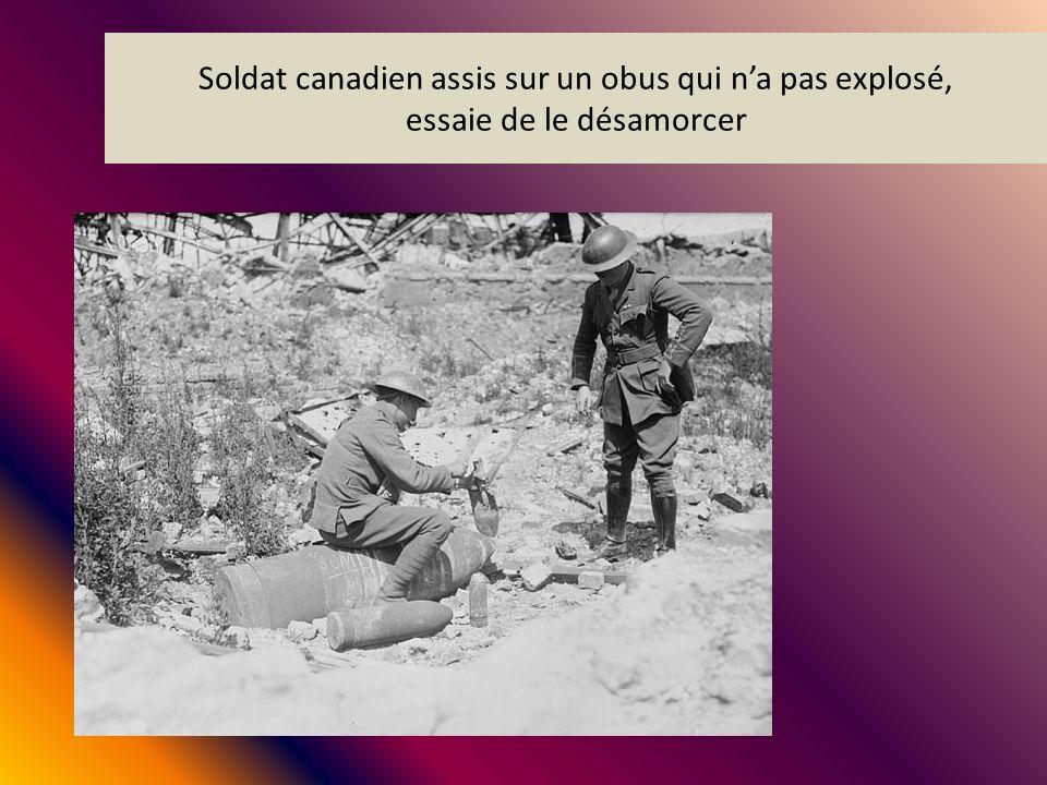 Soldat canadien assis sur un obus qui n'a pas explosé, essaie de le désamorcer