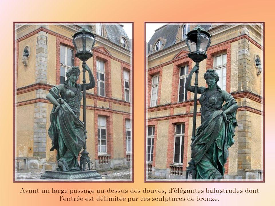 Avant un large passage au-dessus des douves, d'élégantes balustrades dont l'entrée est délimitée par ces sculptures de bronze.