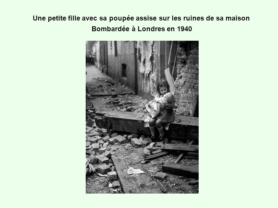 Une petite fille avec sa poupée assise sur les ruines de sa maison