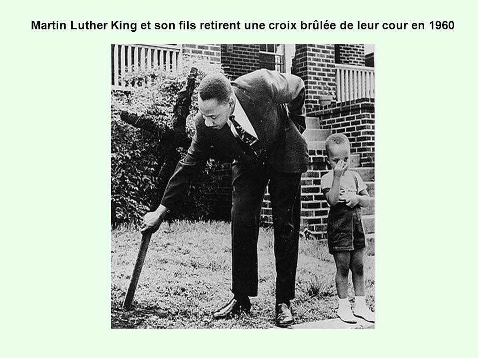 Martin Luther King et son fils retirent une croix brûlée de leur cour en 1960