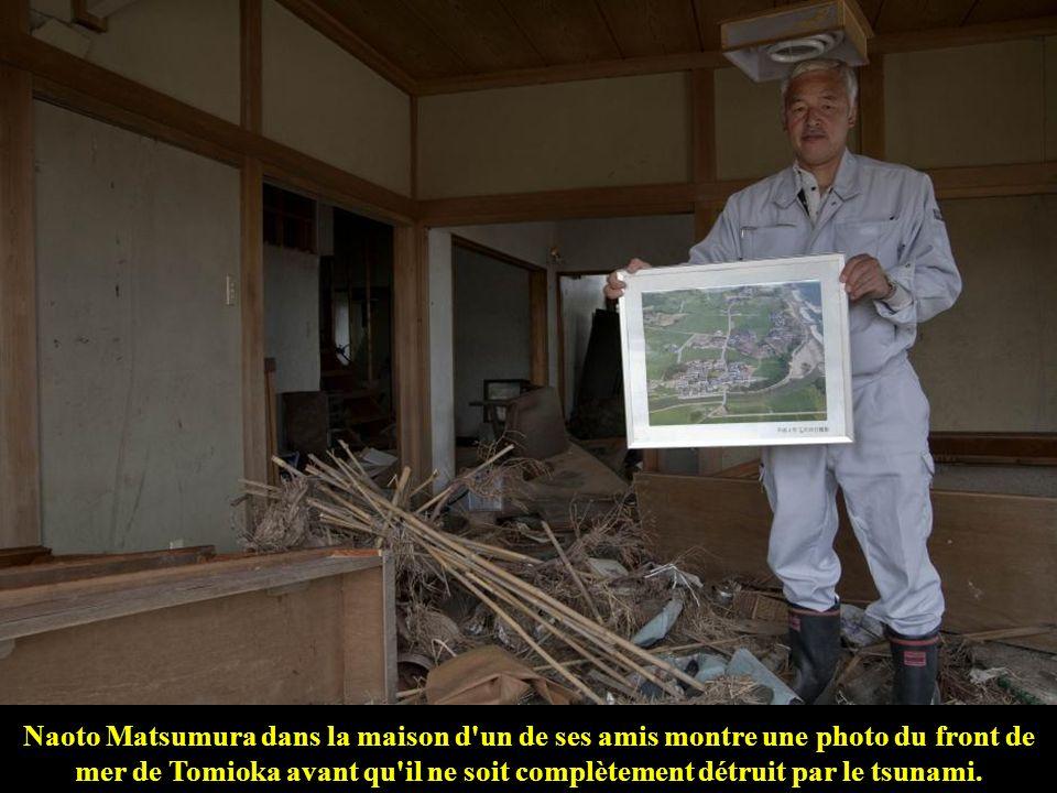 Naoto Matsumura dans la maison d un de ses amis montre une photo du front de mer de Tomioka avant qu il ne soit complètement détruit par le tsunami.