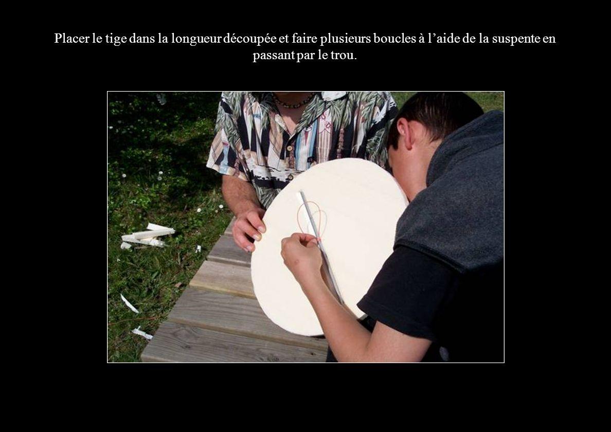 Placer le tige dans la longueur découpée et faire plusieurs boucles à l'aide de la suspente en passant par le trou.
