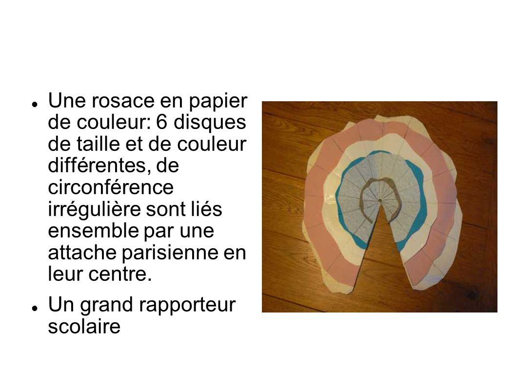 Une rosace en papier de couleur: 6 disques de taille et de couleur différentes, de circonférence irrégulière sont liés ensemble par une attache parisienne en leur centre.