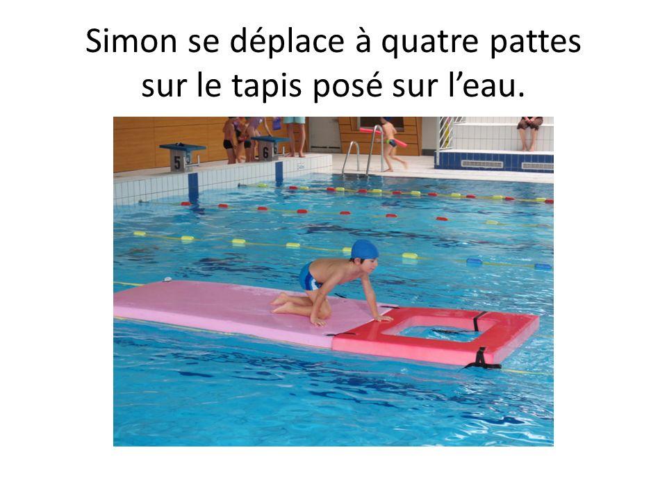 Simon se déplace à quatre pattes sur le tapis posé sur l'eau.
