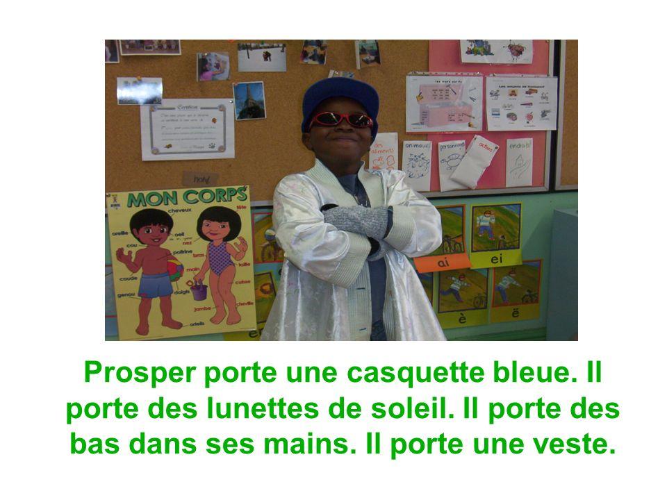 Prosper porte une casquette bleue. Il porte des lunettes de soleil