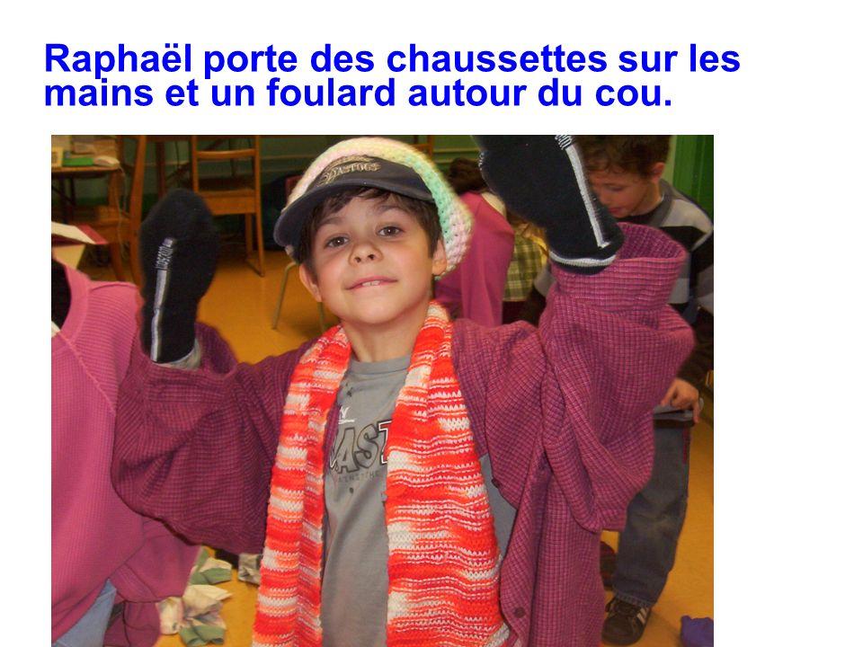 Raphaël porte des chaussettes sur les mains et un foulard autour du cou.