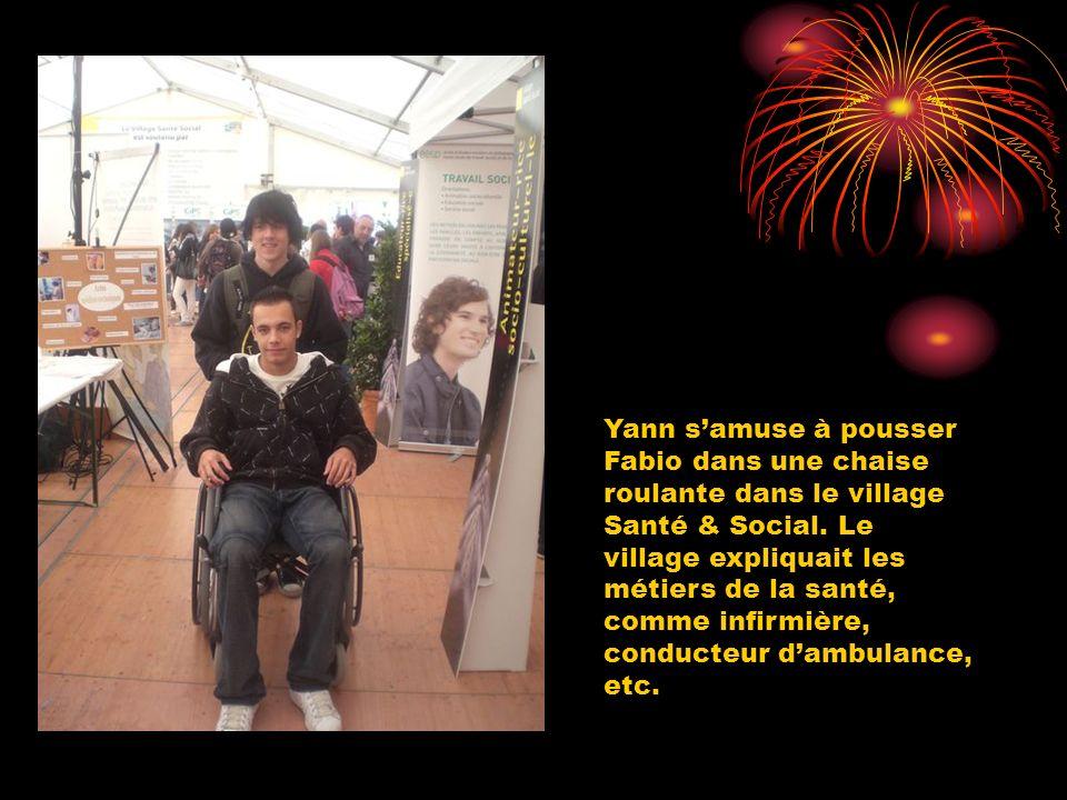 Yann s'amuse à pousser Fabio dans une chaise roulante dans le village Santé & Social.
